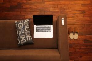 Formation en ligne : ordinateur posé sur un divan accompagné d'un crayon, d'une télécommande. Des pantoufles sont disposées sur le sol.