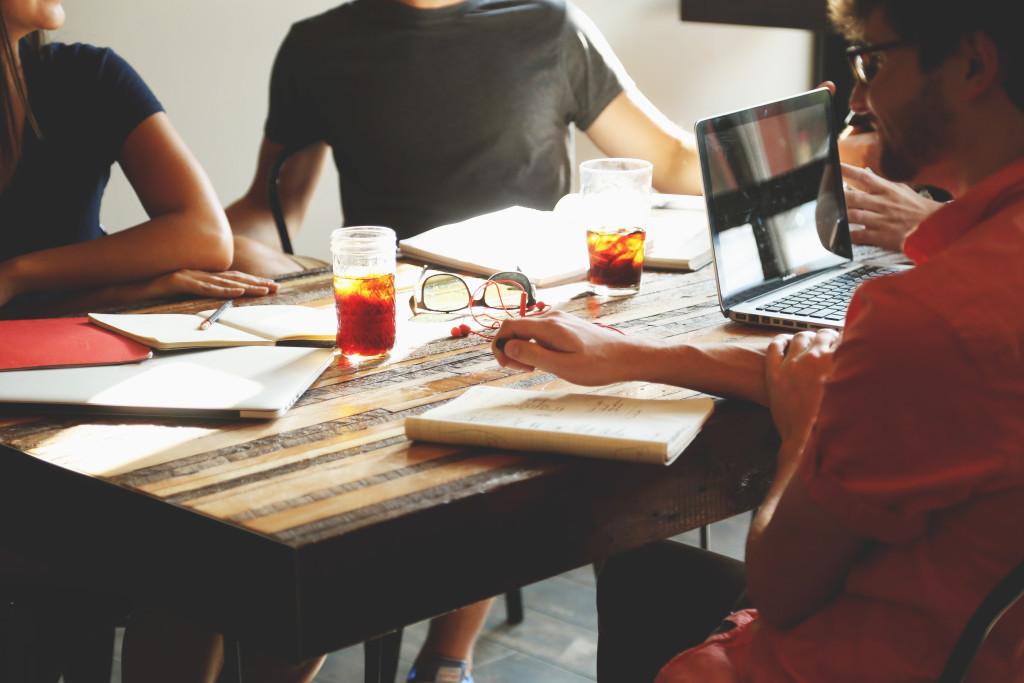 Groupe de travail autour d'une table avec ordinateur et crayons papier